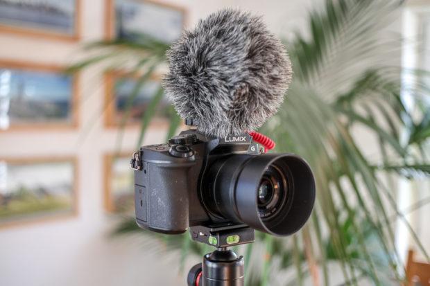 Das typische Video-Mikrofon sitzt mit Fell-Puschel gegen Windgeräusche auf der Kamera.